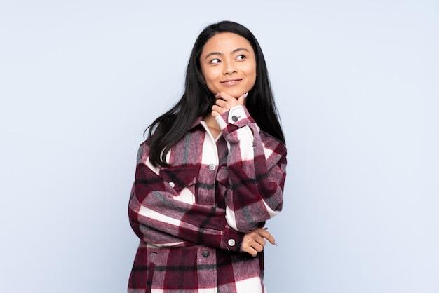 Женщина подростка изолированная на сини думая идея пока смотрящ вверх
