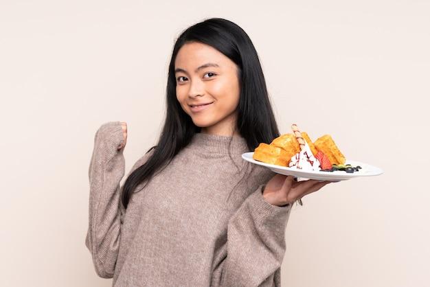 Девушка подростка держа вафли изолированными на бежевом указывая к стороне для того чтобы представить продукт