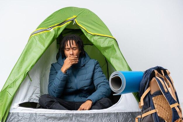 Молодой человек афроамериканца внутри зеленой палатки зевая