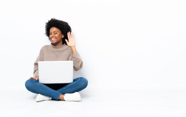 幸せな表情で手で敬礼床に座ってラップトップを持つ若い女性