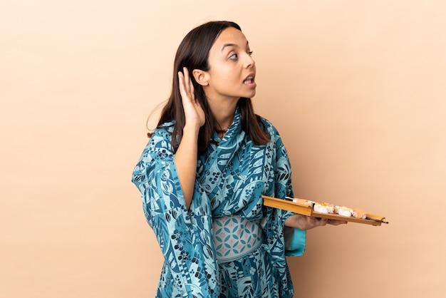 Женщина, носящая кимоно и держащая суши над изолированным слушанием к чему-то, кладя руку на ухо