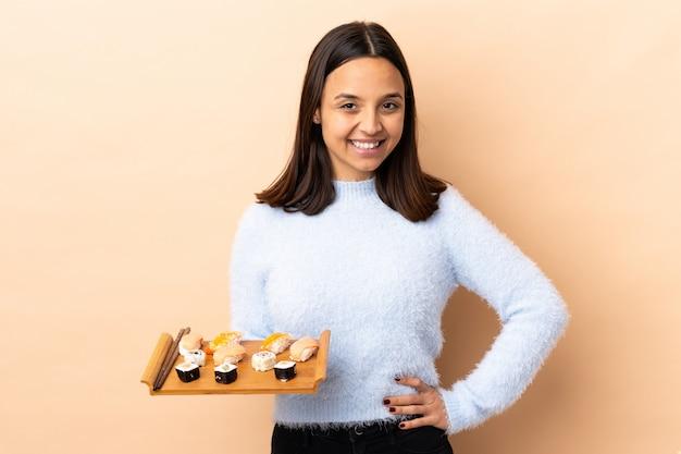 若いブルネットの混血女性が腰に腕で孤立したポーズで寿司を置くと笑顔