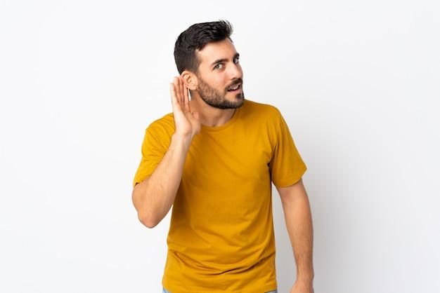 Молодой красивый мужчина с бородой, изолированные на белом, слушая что-то, положив руку на ухо