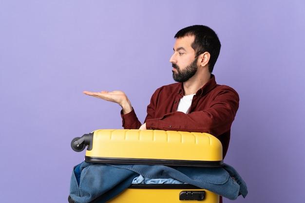 孤立した壁にスーツケースをやっている男
