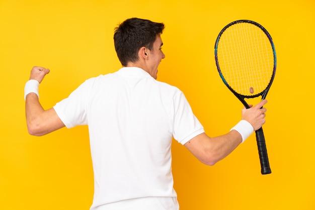 Молодой человек делает теннис над изолированной стеной