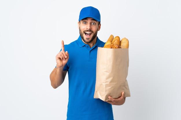 素晴らしいアイデアを指している白い壁に分離されたパンの完全な袋を保持している配達人