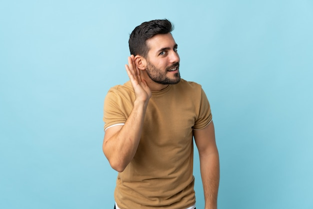 Молодой красивый мужчина с бородой на изолированной стене, слушая что-то, положив руку на ухо