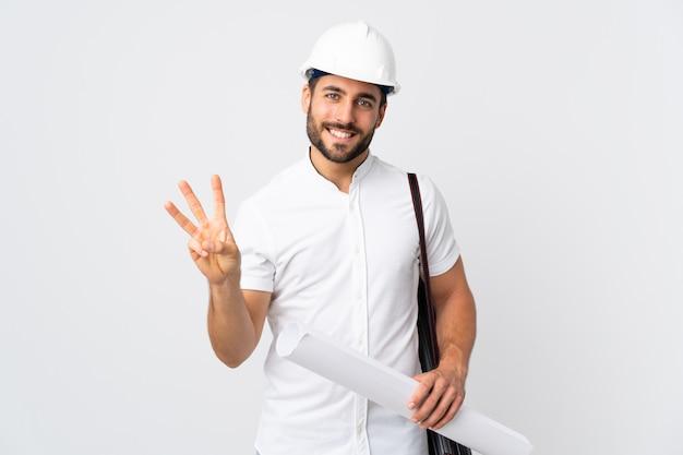 Молодой архитектор человек с шлемом и проведение чертежи, изолированные на белой стене счастливым и считая три пальцами