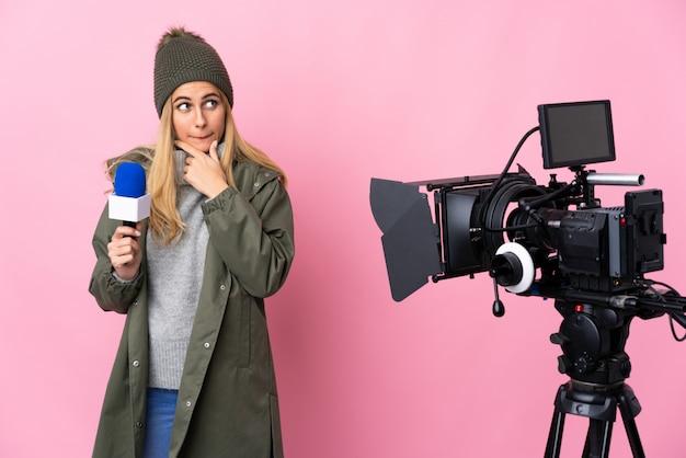 マイクを持っていると疑問と考えを持つ孤立したピンクの壁にニュースを報告するレポーターの女性