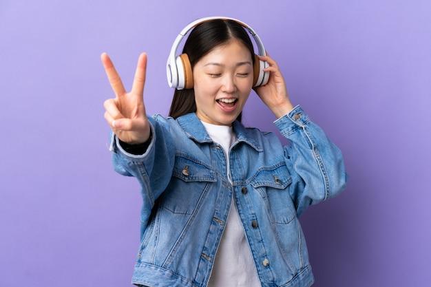 Молодая китайская женщина над изолированной фиолетовой стеной слушая музыка и петь