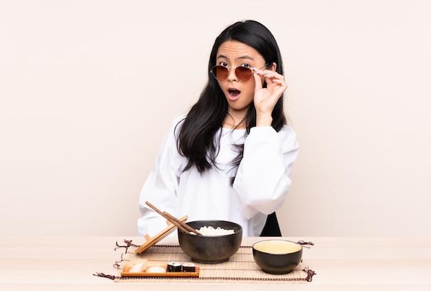Молодая азиатская женщина есть над изолированной стеной