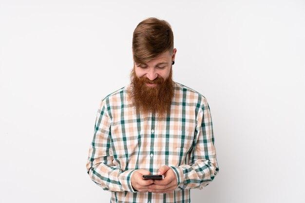 携帯電話でメッセージを送信する孤立した白い壁に長いひげを持つ赤毛の男