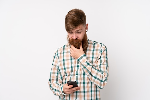 孤立した白い壁を考えてメッセージを送信する長いひげを持つ赤毛の男