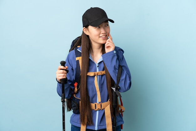 Молодая китаянка с рюкзаком и треккинг поляков над синей стеной, думая идея, глядя вверх