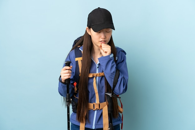 Молодая китаянка с рюкзаком и треккинговыми палками над синей стеной много кашляет