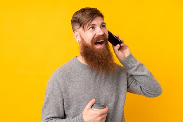 携帯電話との会話を維持する孤立した黄色の壁に長いひげを持つ赤毛の男