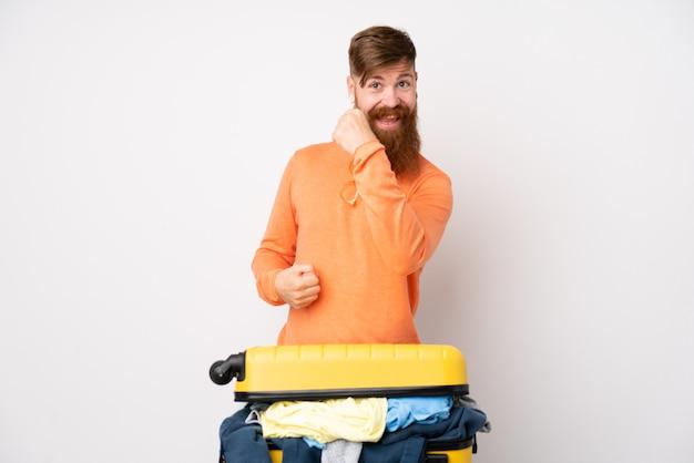 Человек путешественника с чемоданом, полным одежды над изолированной белой стеной, празднует победу