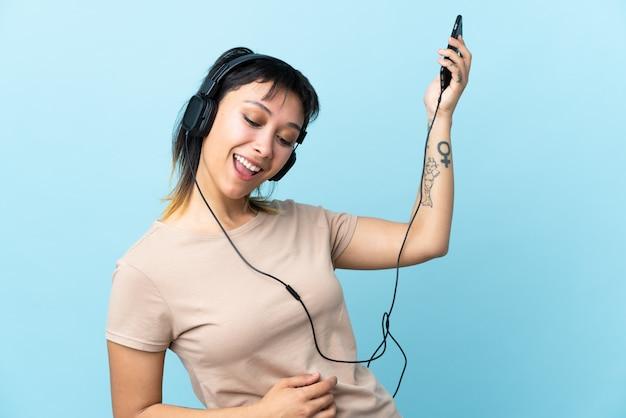 音楽を聴くとギターのジェスチャーを行う孤立した青い背景上のウルグアイの少女