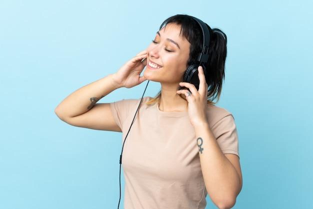 Молодая уругвайская девушка над изолированной голубой предпосылкой слушая музыка и пея