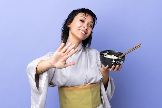 Молодая женщина носить кимоно на изолированных синем фоне салютов с рукой с счастливым выражением, держа миску лапши с палочками для еды