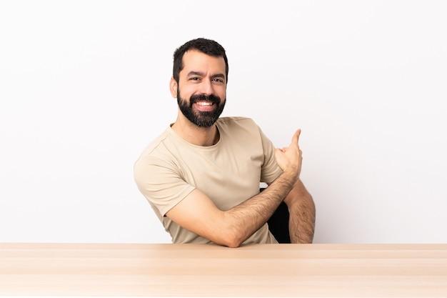 Кавказский мужчина с бородой в таблице, указывая назад