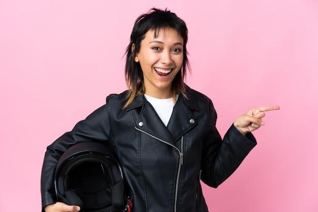 Молодая уругвайская женщина с мотоциклетным шлемом на розовом фоне удивила и указала пальцем в сторону