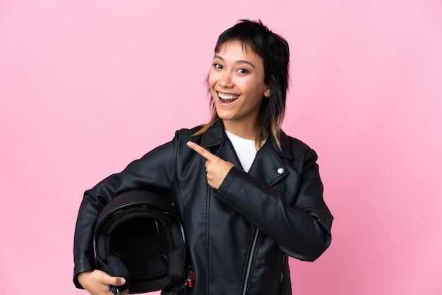 Молодая уругвайская женщина, держащая мотоциклетный шлем над розовым фоном, указывая пальцем в сторону