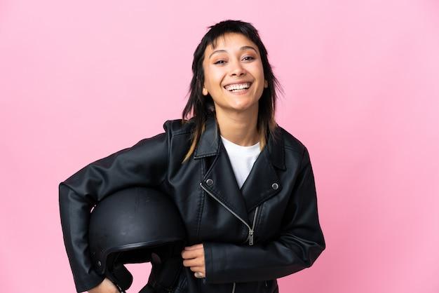 Молодая уругвайская женщина, держащая мотоциклетный шлем над изолированным розовым фоном смеха