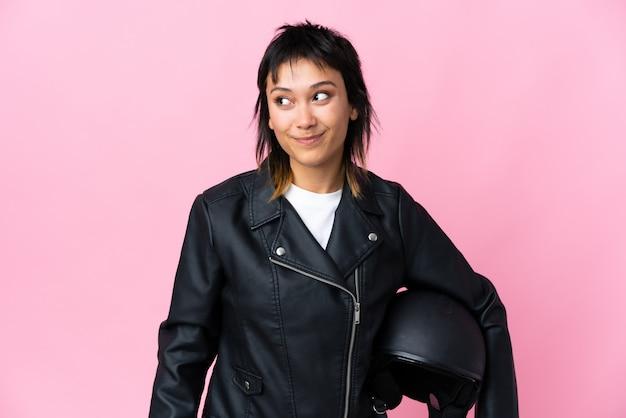 Молодая уругвайская женщина, держащая мотоциклетный шлем над изолированным розовым фоном, стоит и смотрит в сторону