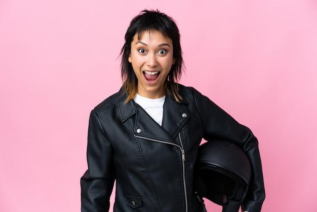 Молодая уругвайская женщина, держащая мотоциклетный шлем, на розовом фоне с удивленным выражением лица