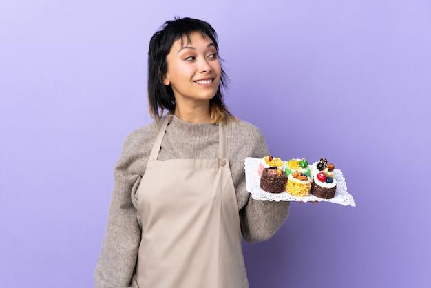 Молодая уругвайская женщина держит много различных мини-пирожных над фиолетовым фоном, смеясь и глядя вверх