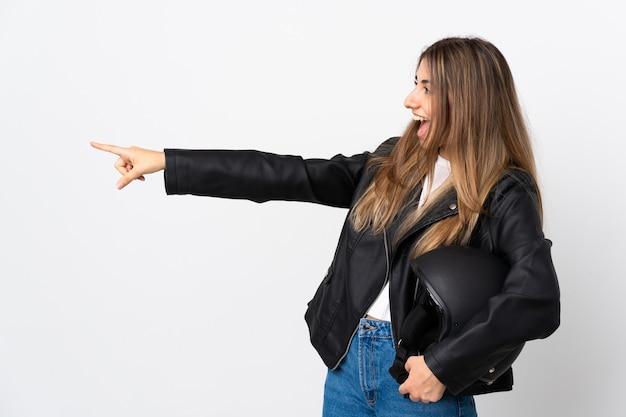 Молодая женщина, держащая мотоциклетный шлем на белом фоне, указывая пальцем в сторону