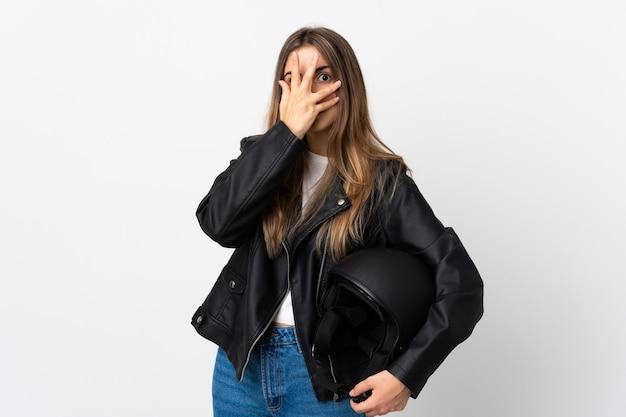 Молодая женщина, держащая мотоциклетный шлем, на белом фоне закрыла глаза и смотрела сквозь пальцы