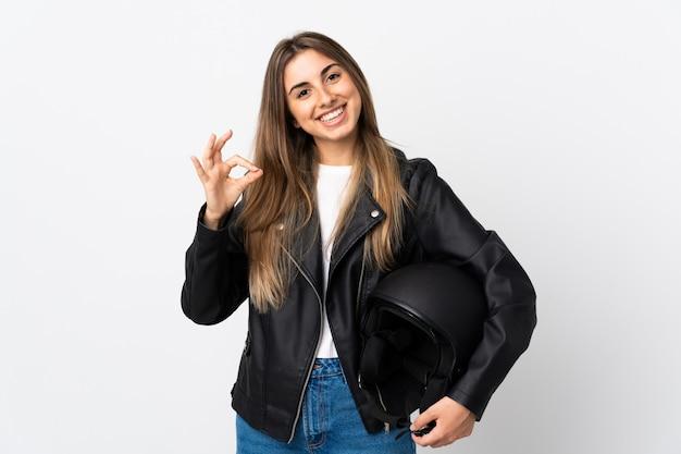 Молодая женщина, держащая мотоциклетный шлем на белом фоне, показывая знак ок с пальцами