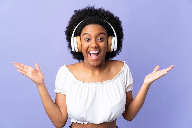Молодая афро-американская женщина изолированная на фиолетовой предпосылке удивленная и слушая музыка