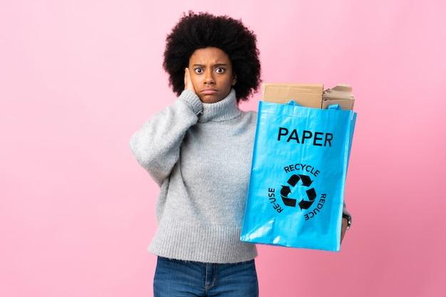 カラフルな背景に分離されたリサイクルバッグを持って若いアフリカ系アメリカ人女性の欲求不満と耳を覆う