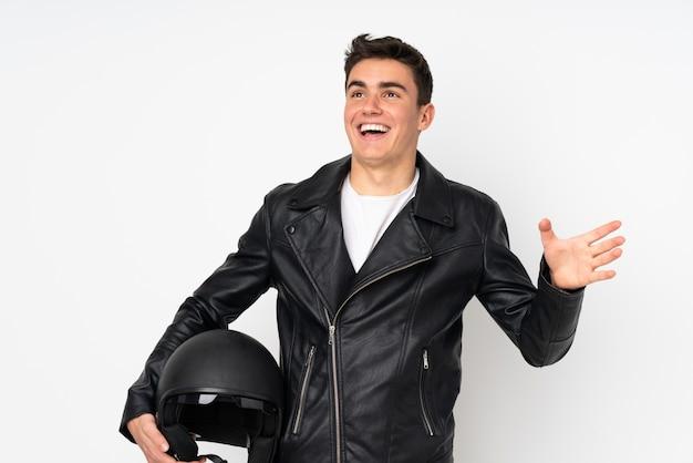 Мужчина держит мотоциклетный шлем на белом фоне с удивленным выражением лица
