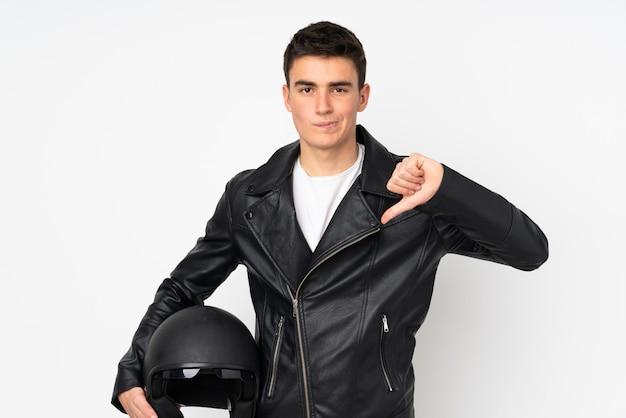 Мужчина держит мотоциклетный шлем на белом фоне, показывая большой палец вниз знак