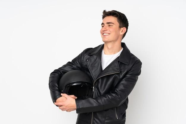 Мужчина держит мотоциклетный шлем на белом фоне, глядя в сторону