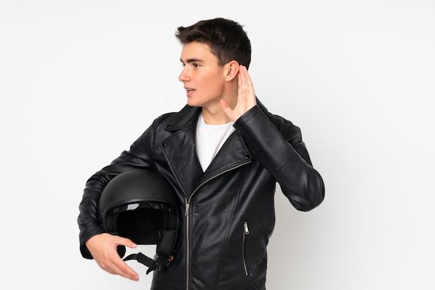 Мужчина держит мотоциклетный шлем на белом фоне, слушая что-то