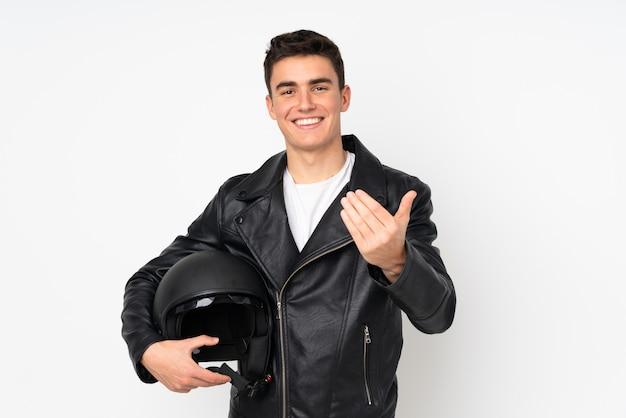 Мужчина держит мотоциклетный шлем на белом фоне, приглашая прийти