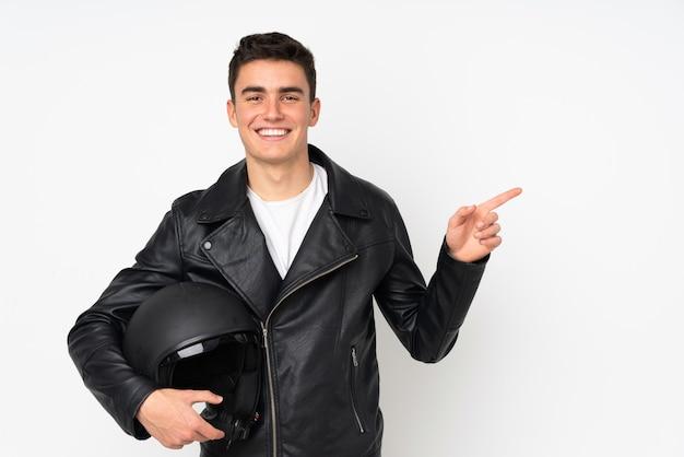 Мужчина держит мотоциклетный шлем на белом фоне, указывая пальцем в сторону