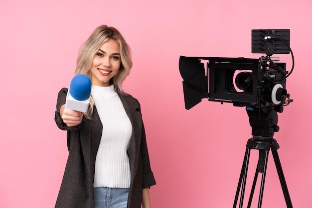 マイクを押しながら孤立したピンクの背景にニュースを報告するレポーター女性