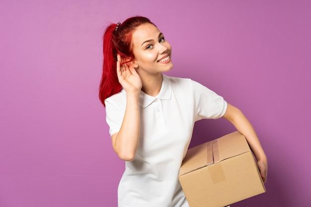 Подросток доставки девушка, изолированных на фиолетовом фоне, слушая что-то, положив руку на ухо