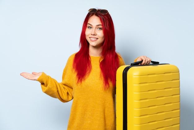 向かって笑顔を見ながらアイデアを提示する青色の背景に分離されたスーツケースを持って旅行者の女の子