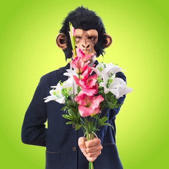 カラフルな背景に花束を保持している猿の男