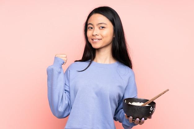 Азиатская женщина подросток, изолированных на бежевом фоне, указывая на сторону, чтобы представить продукт, держа миску лапши с палочками для еды