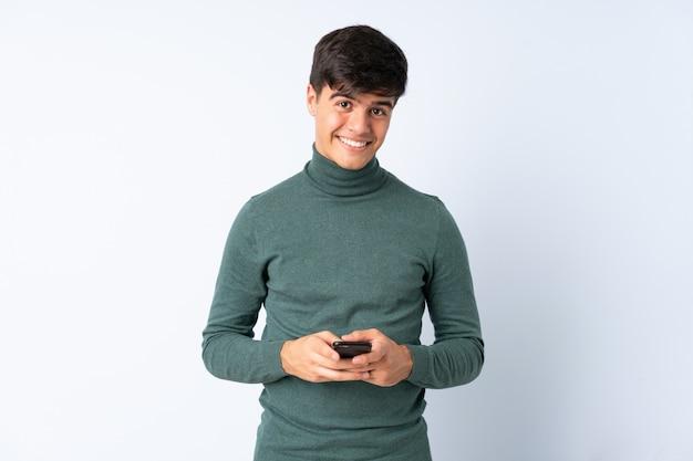 携帯電話でメッセージを送信する孤立した青い背景上のハンサムな男