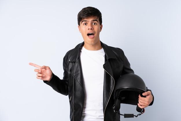 Человек с мотоциклетным шлемом на синем фоне удивлен и указывает пальцем в сторону