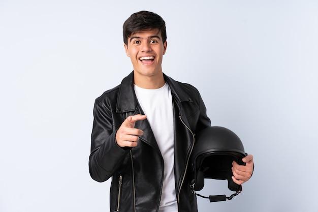 孤立した青い背景上のオートバイのヘルメットを持つ男はあなたに指を指す